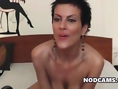 short haired performer in high heels strips